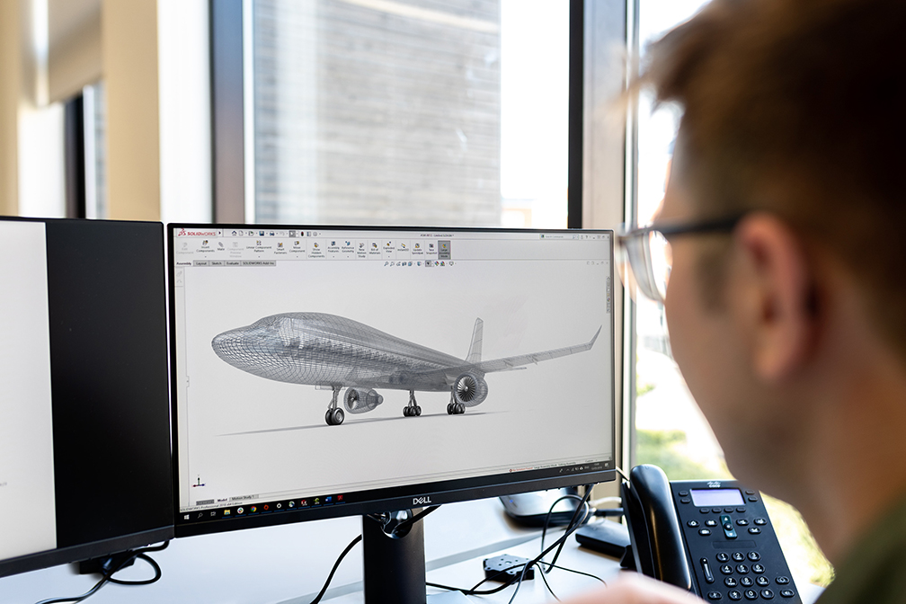 Engineer looking at aircraft engineering design on monitor.